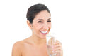 Smiling brunette holding glass of water and looking at camera on white background Royalty Free Stock Photo