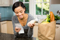Smiling brunette holding receipt and milk Royalty Free Stock Photo