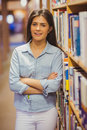 Smiling brunette student standing next to bookshelves with arms crossed Royalty Free Stock Photo