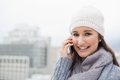 Smiling brunette with winter clothes on having a call outdoors cold grey day Stock Photo