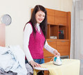 Smiling brunette woman ironing with iron Royalty Free Stock Photo