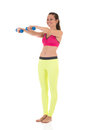 Smiling brunette woman in sports neon yellow leggings and pink bra doing complex exercises for muscles of hands using dumbbell Royalty Free Stock Photo