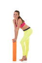 Smiling brunette woman in sports neon yellow leggings and pink bra leaning on the rolled orange mat Royalty Free Stock Photo
