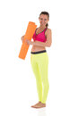 Smiling brunette woman in sports neon yellow leggings and pink bra standing with the orange rolled mat after training Royalty Free Stock Photo