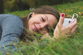 Smiling brunnette woman using cell phone outdoor laying in the grass Stock Images