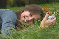 Smiling brunnette woman using cell phone outdoor laying in the grass Stock Photos