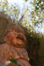 Smiling buddha statue low angle view of the face of a terracotta outdoors looking up through greenery to blue sky Royalty Free Stock Images