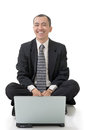 Smiling business man of asian sit and use laptop on ground full length on white background Stock Photos