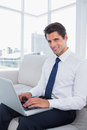 Smiling business man using laptop in a bright office Stock Image