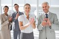 Smiling business people applauding together in the meeting room Stock Photography