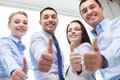 Smiling business people showing thumbs up teamwork success and gesture concept team in office Stock Photography