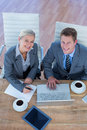 Smiling business people using laptop in the office Royalty Free Stock Photos