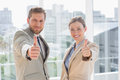 Smiling business team giving thumbs up looking at camera Royalty Free Stock Photography