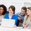 Smiling business team grouped around a laptop diverse multiethnic as they share their thoughts and ideas Royalty Free Stock Images