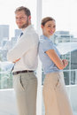 Smiling business team standing back to back in bright office Stock Photo