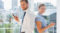 Smiling business team standing back to back and texting in a bright office Stock Photography