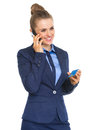 Smiling business woman with credit card talking cell phone isolated on white Royalty Free Stock Photo
