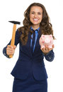 Smiling business woman giving piggy bank and hammer isolated on white Royalty Free Stock Photo