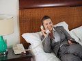 Smiling business woman laying on bed talking phone in hotel room Stock Photography