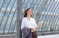 Smiling business woman with mobile phone looking away portrait of a Stock Photos