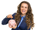Smiling business woman putting coin into piggy bank isolated on white Stock Photo