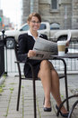 Smiling business woman reads newspaper at outdoor coffee shop Royalty Free Stock Photo