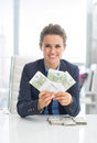 Smiling business woman showing money packs in office Royalty Free Stock Image