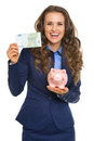 Smiling business woman showing one hundred euros and piggy bank isolated on white Royalty Free Stock Image