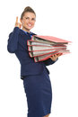 Smiling business woman with stack of folders pointing on copy space Stock Photography