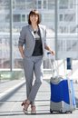 Smiling business woman standing at airport with bag full length portrait of a Royalty Free Stock Images