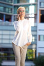 Smiling business woman walking outside with mobile phone Royalty Free Stock Photo