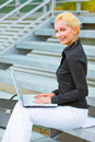 Smiling business woman working on laptop Stock Photo