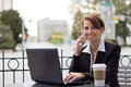 Smiling business woman working on telephone at outdoor coffee sh Royalty Free Stock Photo