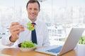 Smiling businessman eating a salad