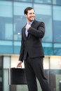 Smiling businessman in front of an office building