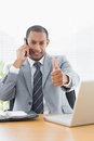 Smiling businessman gesturing thumbs up while on call Royalty Free Stock Photography
