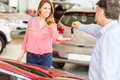 Smiling businessman giving car key to happy customer Royalty Free Stock Photo