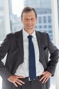 Smiling businessman with his hands on hips in office Royalty Free Stock Images