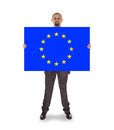 Smiling businessman holding a big card flag of the european uni union isolated on white Stock Images