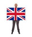 Smiling businessman holding a big card flag of the united kingd kingdom isolated on white Stock Images