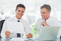 Smiling businessman listening to his intern while explaining doc documents in bright office Royalty Free Stock Images