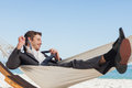 Smiling businessman lying in hamock taking off his tie at beach Royalty Free Stock Photo