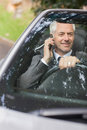 Smiling businessman on the phone driving expensive cabriolet sunny day Royalty Free Stock Images