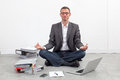 Smiling businessman practicing yoga at office for relaxation Royalty Free Stock Photo