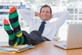 Smiling businessman relaxing with feet on his desk Royalty Free Stock Photo