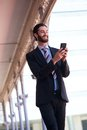 Smiling businessman sending text message on cell phone Royalty Free Stock Photo