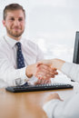 Smiling businessman shaking hands with a co worker sitting at his desk Stock Photo