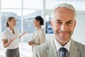 Smiling businessman standing in front of colleagues talking together their office Royalty Free Stock Images