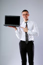 Smiling businessman standing with laptop