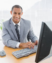 Smiling businessman using computer at office Stock Photos